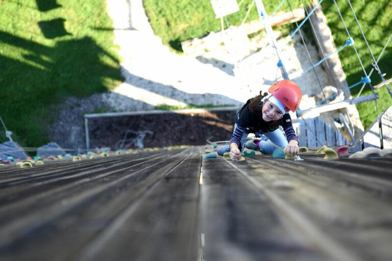 Kind an 15 Meter hoher Kletterwand im Klettergarten Guenzburg